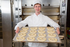 Baker in bakery with baking plate full of pretzels. Baker in bakehouse or bakery presenting baking plate with pretzel dough Stock Photography