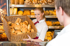 Baker in bakery with basket full of bread Stock Image