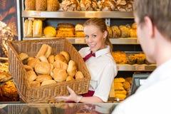 Baker in bakery with basket full of bread Stock Image