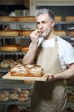 Baker in the bakery. A handsome baker with a loaf of fresh bread standing in the bakery royalty free stock photo