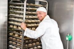 Baker at bakery putting rack of fresh dough in refrigerator Stock Image