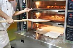 Baker bakes bread in oven Stock Photos