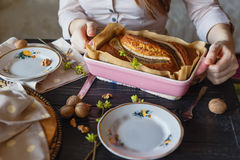 The baker with banana cake. Close-up view girls hands with baking tray. The baker with banana cake. Close-up view girls hands with baking tray Royalty Free Stock Images