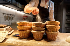 Baker with baskets for dough rising at bakery. Food cooking, baking and people concept - chef or baker preparing baskets while dough rising at bakery kitchen Stock Image