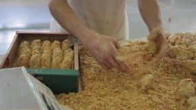 Baker beende stukken deeg in broodcrumbs en pakken in een doos uit stock footage