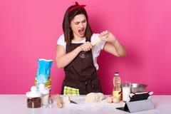 Baker bereidt pastei voor, in bakkerij wordt gevuld, heeft ??n of ander probleem met consistentie van deeg, kan geen broodje beel stock fotografie