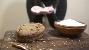 Baker blowing flour on freshly baked loaf of homemade organic sourdough rye bread lying on wooden table stock video
