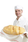 Baker with bread. Baker in uniform with big loaf of bread stock photography