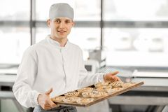 Baker with buns at the manufacturing. Portrait of a handsome baker with tray full of freshly baked buns standing at the bakery manufacturing royalty free stock image