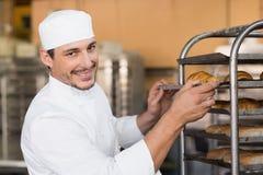 Baker checking freshly baked bread Stock Images