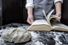 Baker chef looking for a recipe in a cookbook. In the foreground is piece of dough on the black wooden table covered with flour Stock Photography
