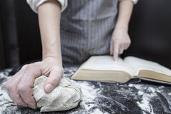 Baker chef looking for a recipe in a cookbook helping finger. In the foreground is piece of dough on the black wooden table covered with flour Stock Photos