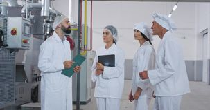 Baker chef old man and young engineer guy with beard have a conversation with their assistance in the middle of bakery. Industry factory. 4k stock footage