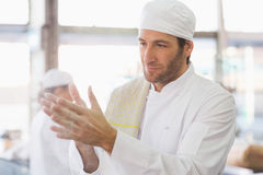 Baker clapping flour from his hands Royalty Free Stock Images