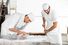 Baker Cleaning Table While Collega die Zwabber gebruiken royalty-vrije stock foto's