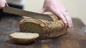 Baker coupant le pain fraîchement cuit au four du pain de seigle organique fait maison de levain avec le couteau de pain clips vidéos