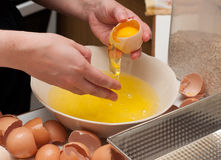 Baker cracking an egg. Stock Images