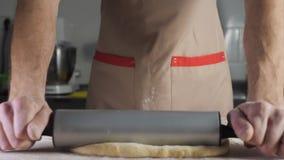 Baker de chef-kok rolt het deeg met de deegrol op de lijst stock video