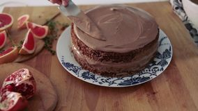 Baker decorated chocolate cake with chocolate topping, kitchen, the process of cooking cake stock footage