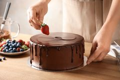 Baker decorating fresh delicious homemade chocolate. Cake with berries on table, closeup royalty free stock photos