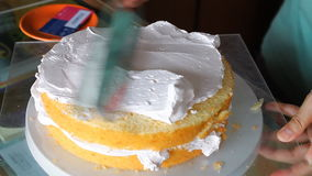 Baker decorating top layer with whipped cream stock video