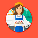 Baker delivering cakes. A female baker holding a box of cakes. A baker delivering cakes. Baker with cupcakes standing on the background of delivery truck Royalty Free Stock Photo