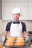 Baker die croissant tonen stock afbeeldingen