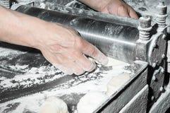 Baker die deeg met machine voor rollend deeg maken Stock Afbeeldingen