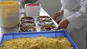 Baker die en pasteigevallen in industriële bakkerij vullen voorbereiden stock videobeelden