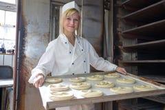 Baker die pretzels zetten in oven in een bakkerij stock afbeelding