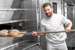 Baker die uit het oven gebakken buckweat brood nemen royalty-vrije stock foto's