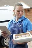 Baker With Digital Tablet Making Home Delivery Of Cupcakes Royalty Free Stock Photos