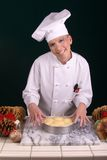 Baker Dinner Rolls. Assertive posed uniformed female Pastry Chef showing dinner rolls for the oven at her baking station amid Christmas ornamentation Royalty Free Stock Photos