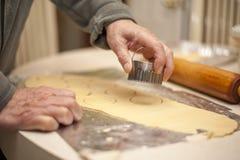 Baker dispose la pâte pour couper des sorties avec le coupeur de biscuit image libre de droits