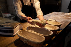 Baker with dough rising in baskets at bakery. Food cooking, baking and people concept - chef or baker putting yeast bread dough into baskets for rising at bakery Stock Photos