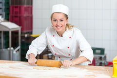 Baker with dough roll working in a bakery Stock Photos
