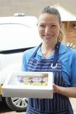 Baker féminin Making Home Delivery des petits gâteaux photographie stock