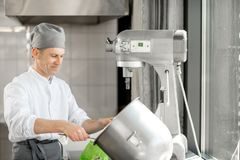 Baker filling confectionery syringe. Making buns at the bakery manufacturing stock images