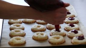 Baker filling pastry with jam in bakery stock footage