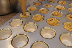 Baker filling tin with pumpkin muffin batter stock photo