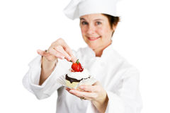 Baker - Finishing Touch. Closeup of a pretty baker holding a delicious strawberry chocolate cheesecake tart.  Shallow depth of field with focus on the strawberry Stock Photos