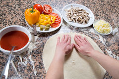 Baker Flattening Dough With Hands And Preparing It For Making Vegetarian Pizza On Marble Table Stock Images