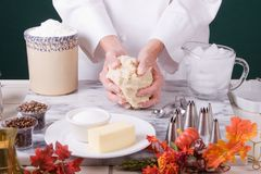 Baker forming pie crust. Assertive composition of a Baker forming pie crust dough with her hands on a cold marble board Royalty Free Stock Image