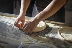 Baker forms a round base for pizza making.  royalty free stock images