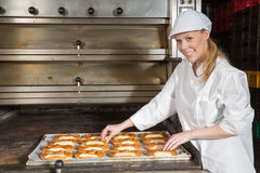 Baker in front of oven with pretzels inside a bakery Royalty Free Stock Images