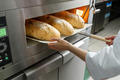 Baker gets hot bread out of the oven Royalty Free Stock Photo