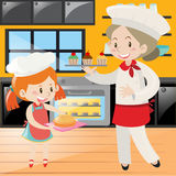 Baker and girl baking in kitchen Stock Photography