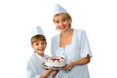 Baker and girl with iced cake. Blond baker and young girl assistant, both in uniform,  smiling and together holding an iced cake with chocolate decoration Royalty Free Stock Photography