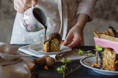 A baker girl pours hot chocolate on an incredibly appetizing piece of cake. Close-up view. Royalty Free Stock Image