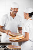 Baker Giving Packed Pizza Breads To Colleague Royalty Free Stock Photos